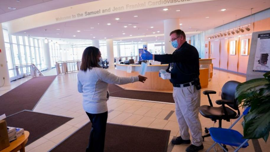 Man with mask handing a mask to woman near Frankel Cardiovascular Center reception desk