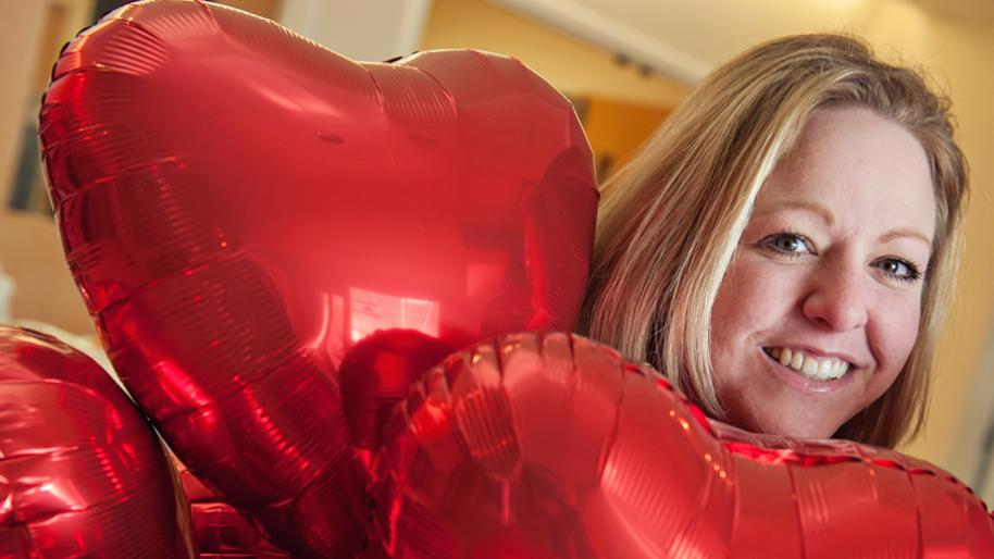 Blonde woman with red foil heart balloons