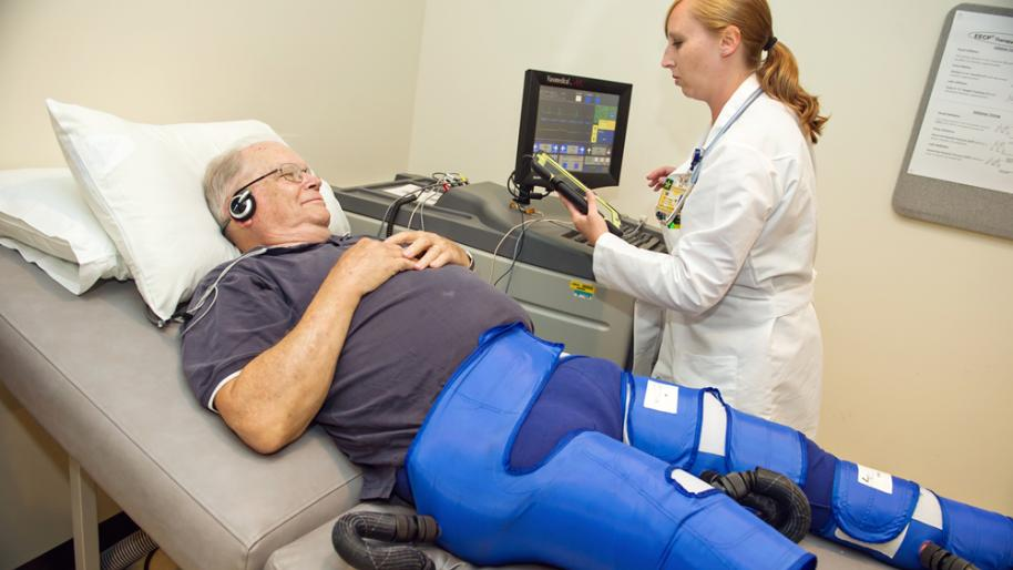Reclining patient attached to compression pants and monitor for EECP treatment