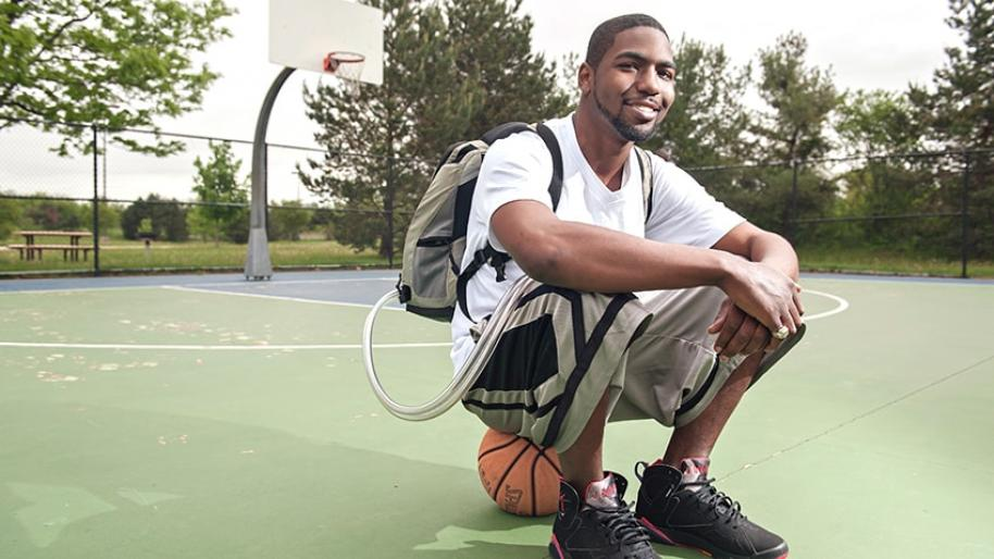 Man with backpack sitting on a basketball on a basketball court