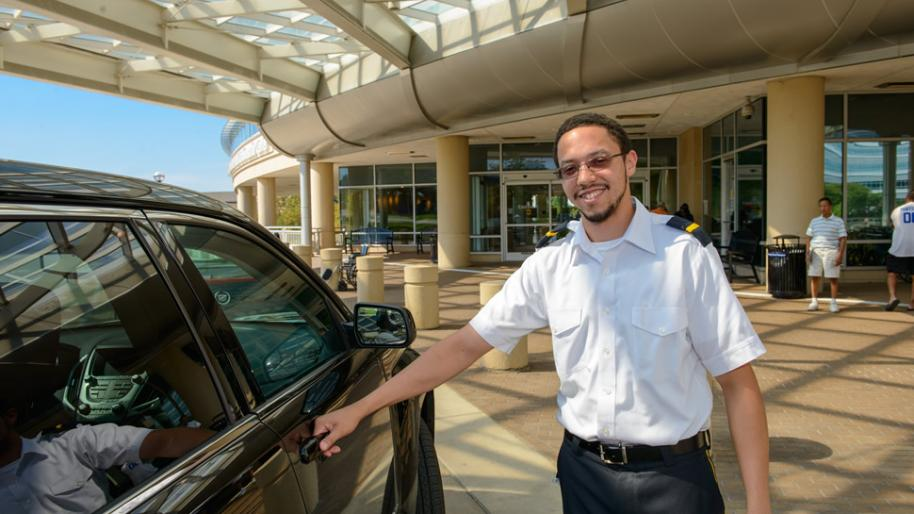 valet parking attendant standing next to a vehicle at the University of Michigan Frankel Cardiovascular Center