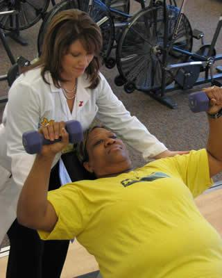 Exercise physiologist and patient with weights