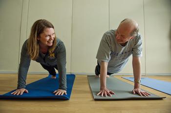 Man and woman doing yoga plank pose