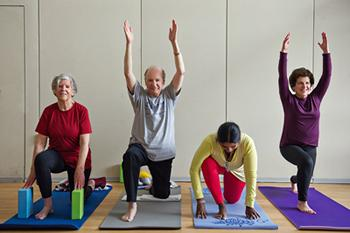 Four yoga class participants on mats